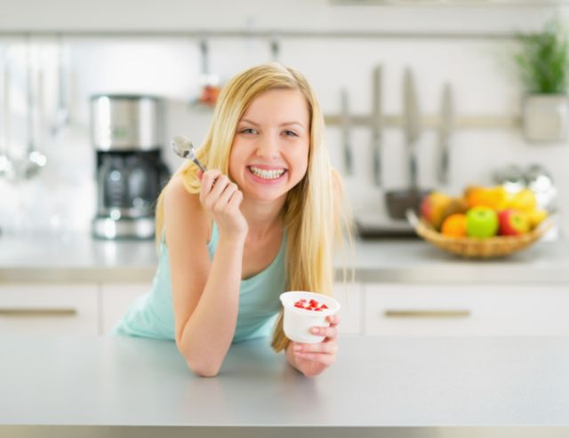 happy young woman eating yogurt in kitchen