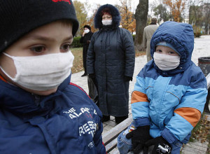 Children wearing protective masks play in central square in Kiev