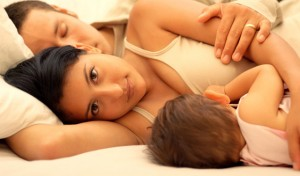 Man and woman sleeping with baby